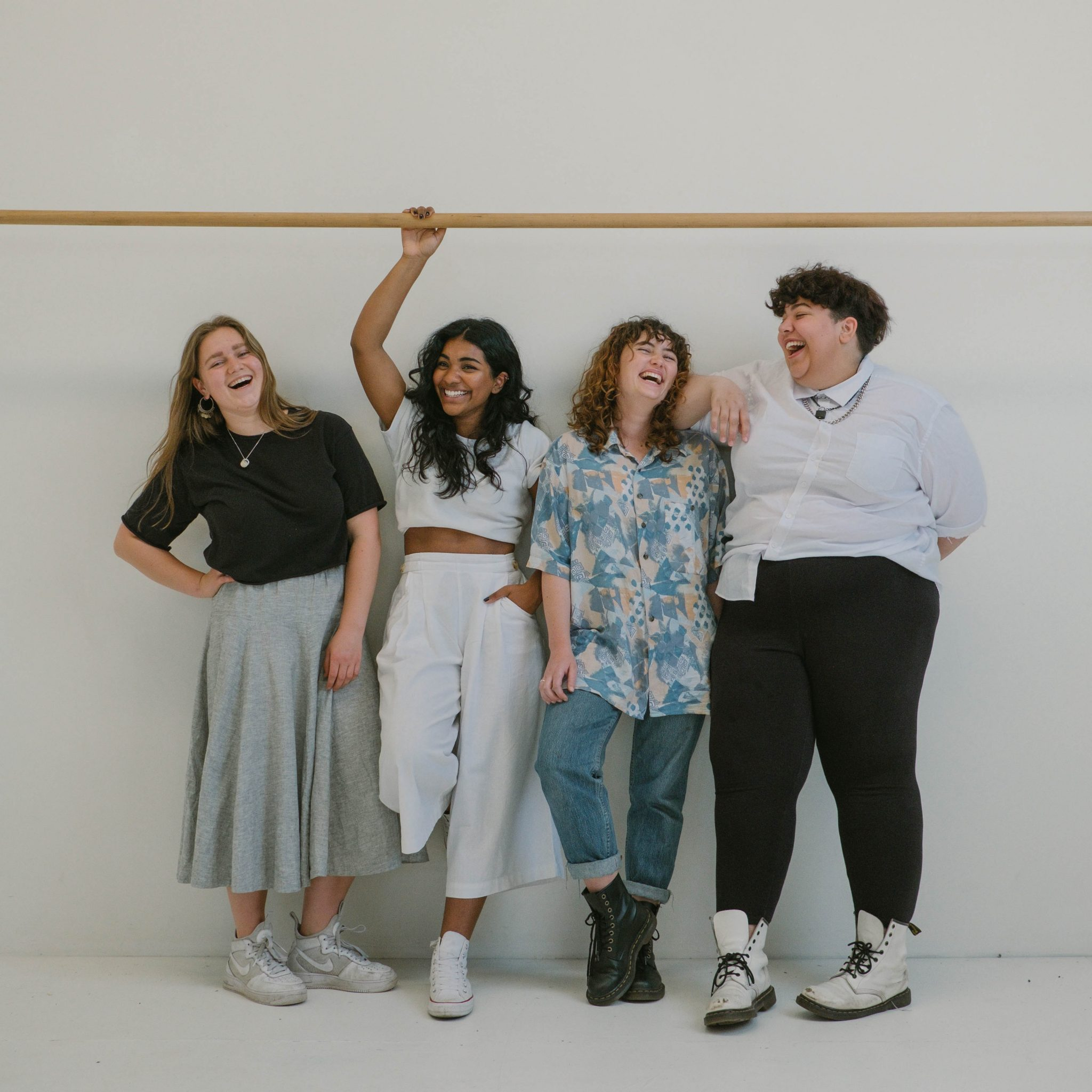 Group of 4 ladies of different body sizes standing against a wall laughing
