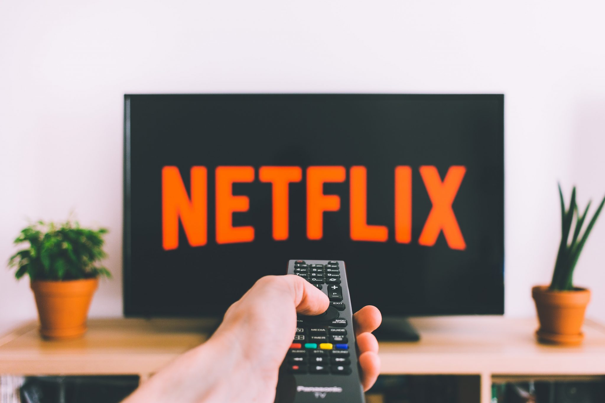 Netflix on a large TV with man pointing controller