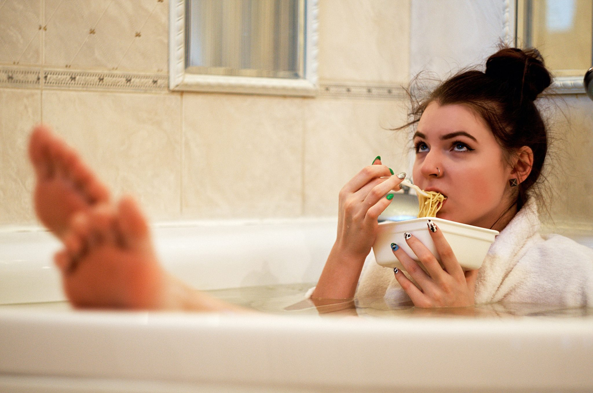 Lady eating noodles in the bath tub, looking a little unhappy
